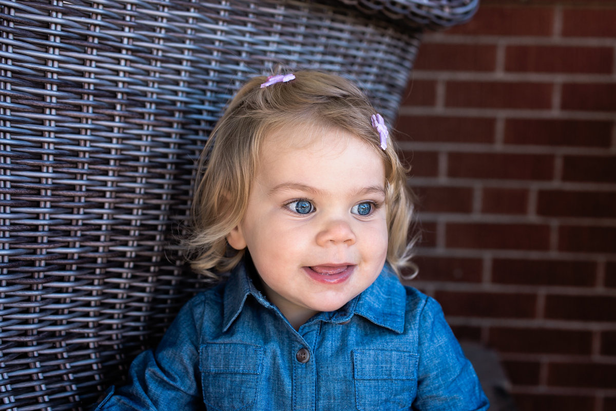 Little girl smiling on front porch during lifestyle family session with Jennifer Blaak Photography