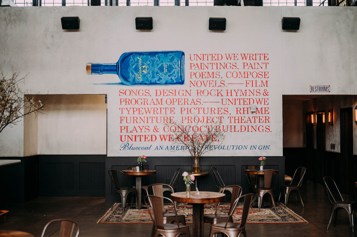 a mural says united we write paintings, paint poems, compose novels. - Film songs, design rock hymns & program operas. - United we typewrite pictures, rhyme furniture, project theater plays & concoct buildings. United we create. Bluecoast an american revolution in gin. at philadelphia distilling company shot by philadelphia wedding photographer alex medvick