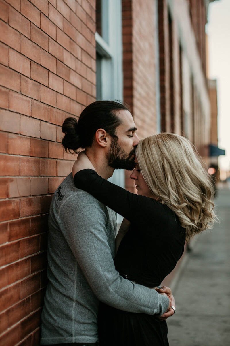 man kissing fiancé on forehead against brick wall downtown
