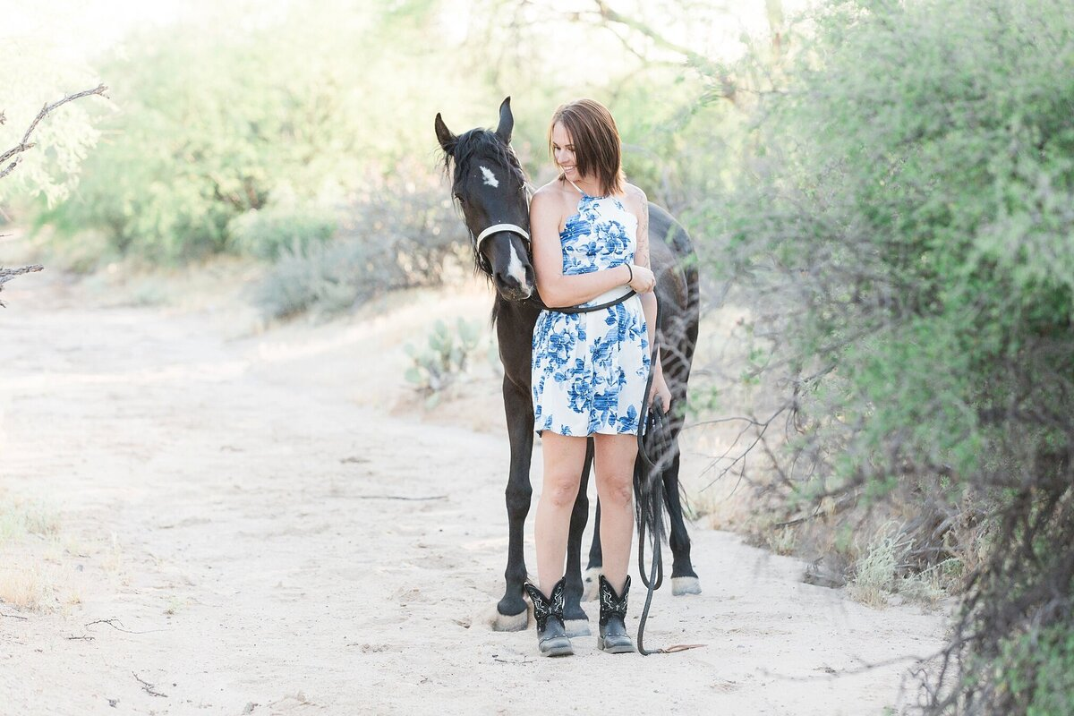 girl standing next to her black horse, looking at each other