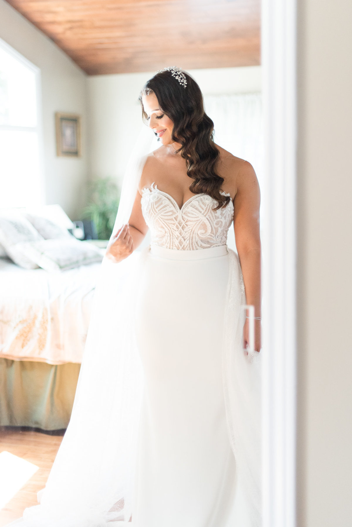 Bride looking in the mirror in her Julie Vino wedding gown before her wedding at The Chanterelle in Thunder Bay