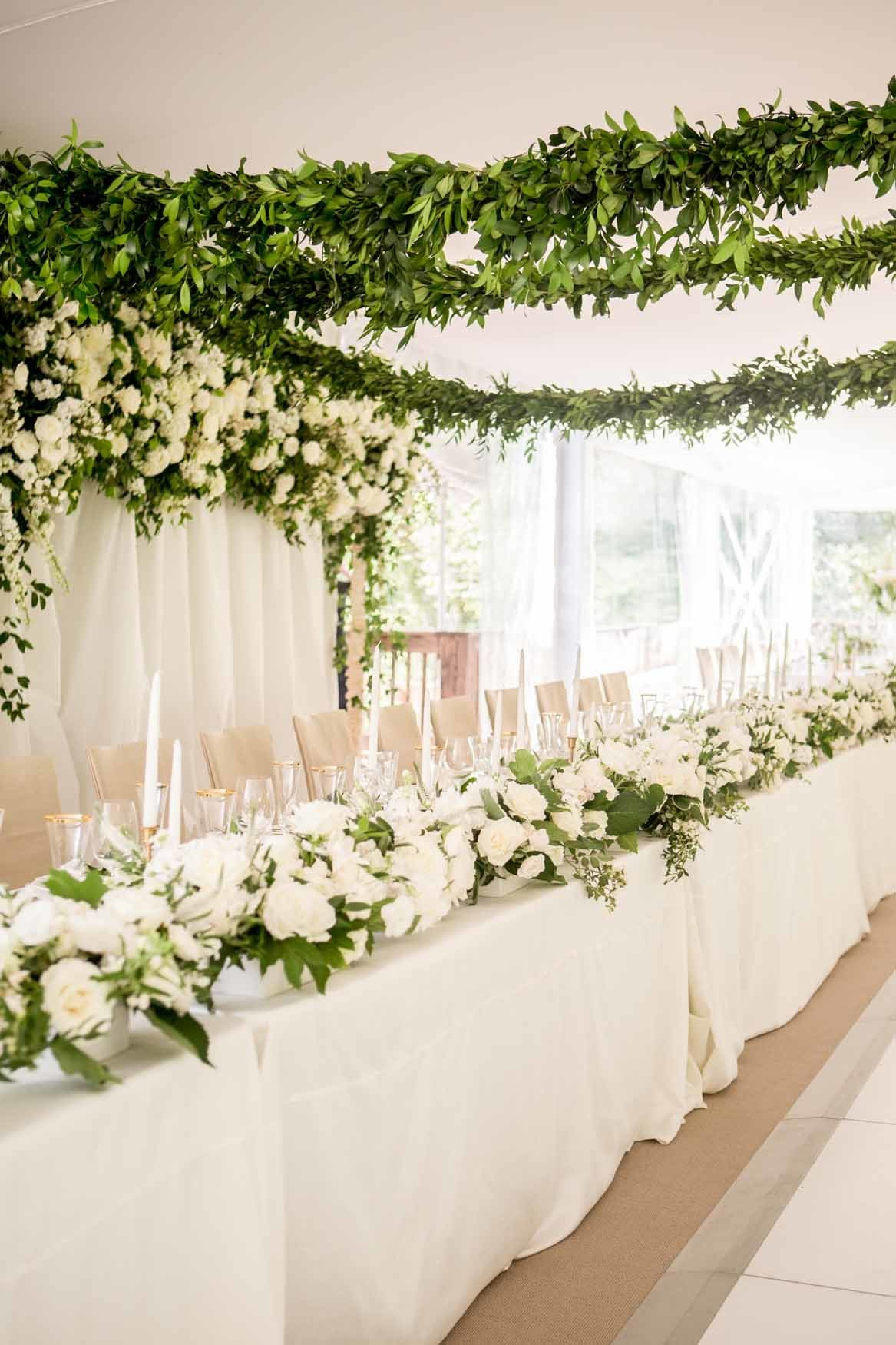 Grand tent wedding head table with white floral  and green garlands on ceiling