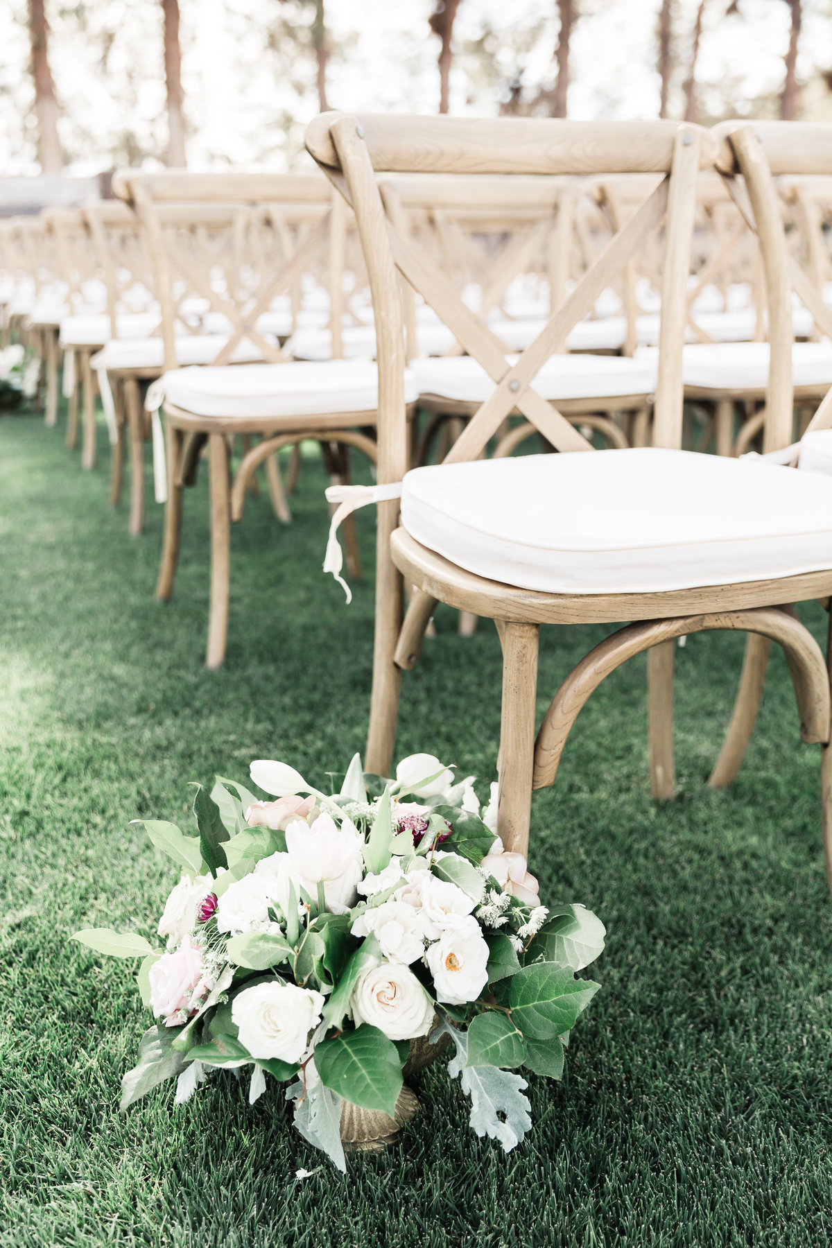 a photo of rustic x back chairs for a wedding ceremony in Las Vegas with a small aisle marker floral centerpiece
