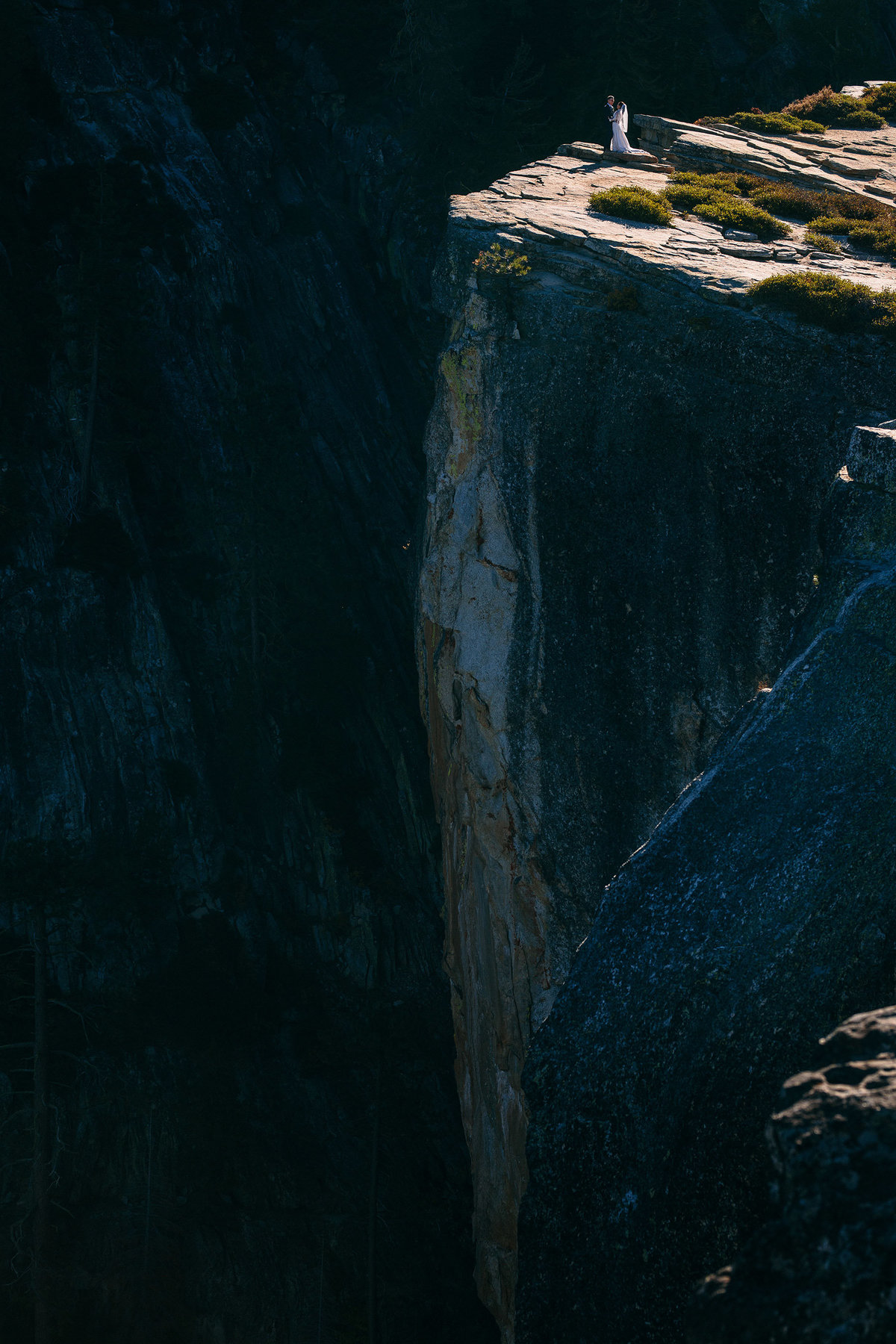 Bride & groom embrace after their sunrise wedding on Taft Point in Yosemite, Ca.