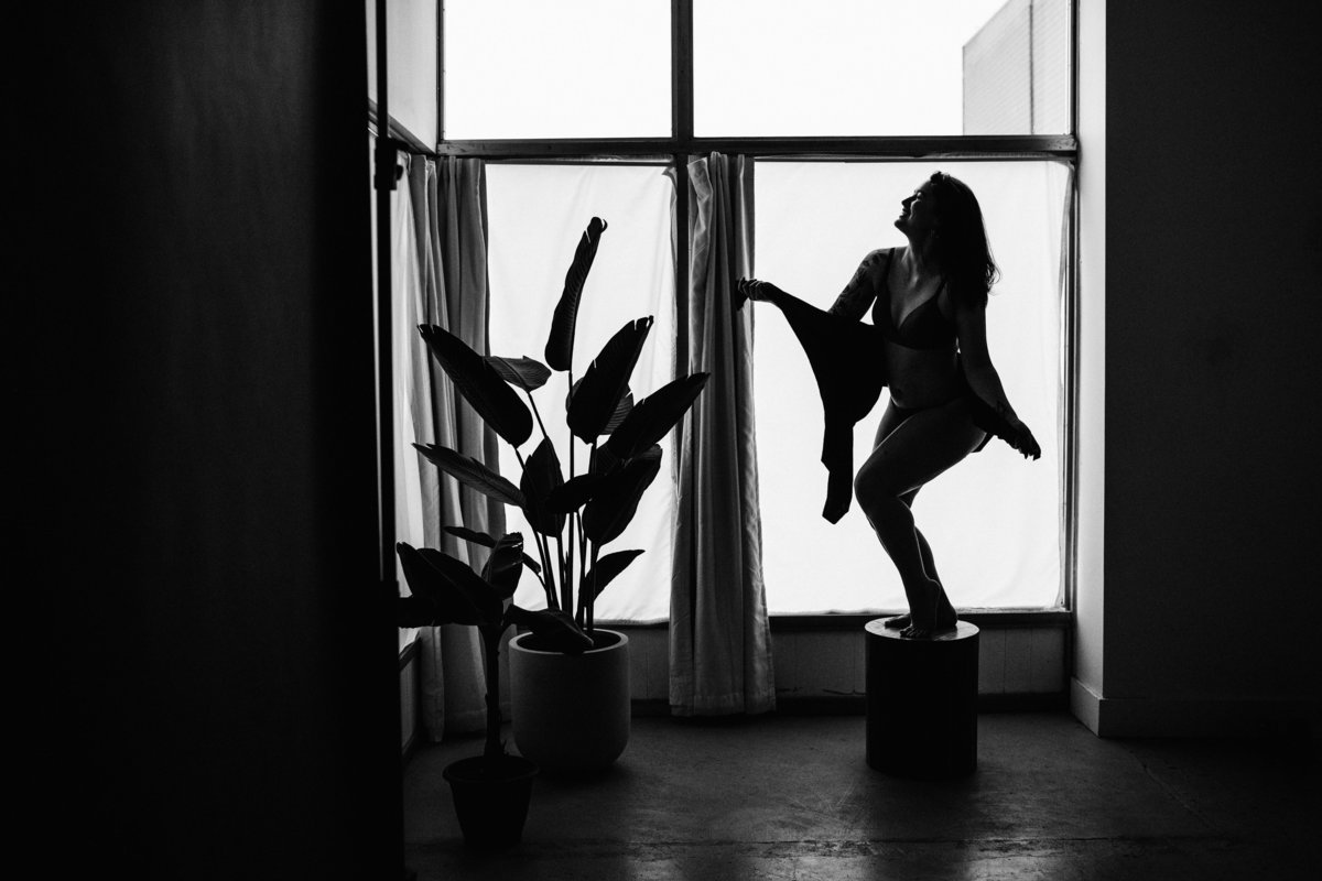 wide shot of silhouetted woman and large houseplant
