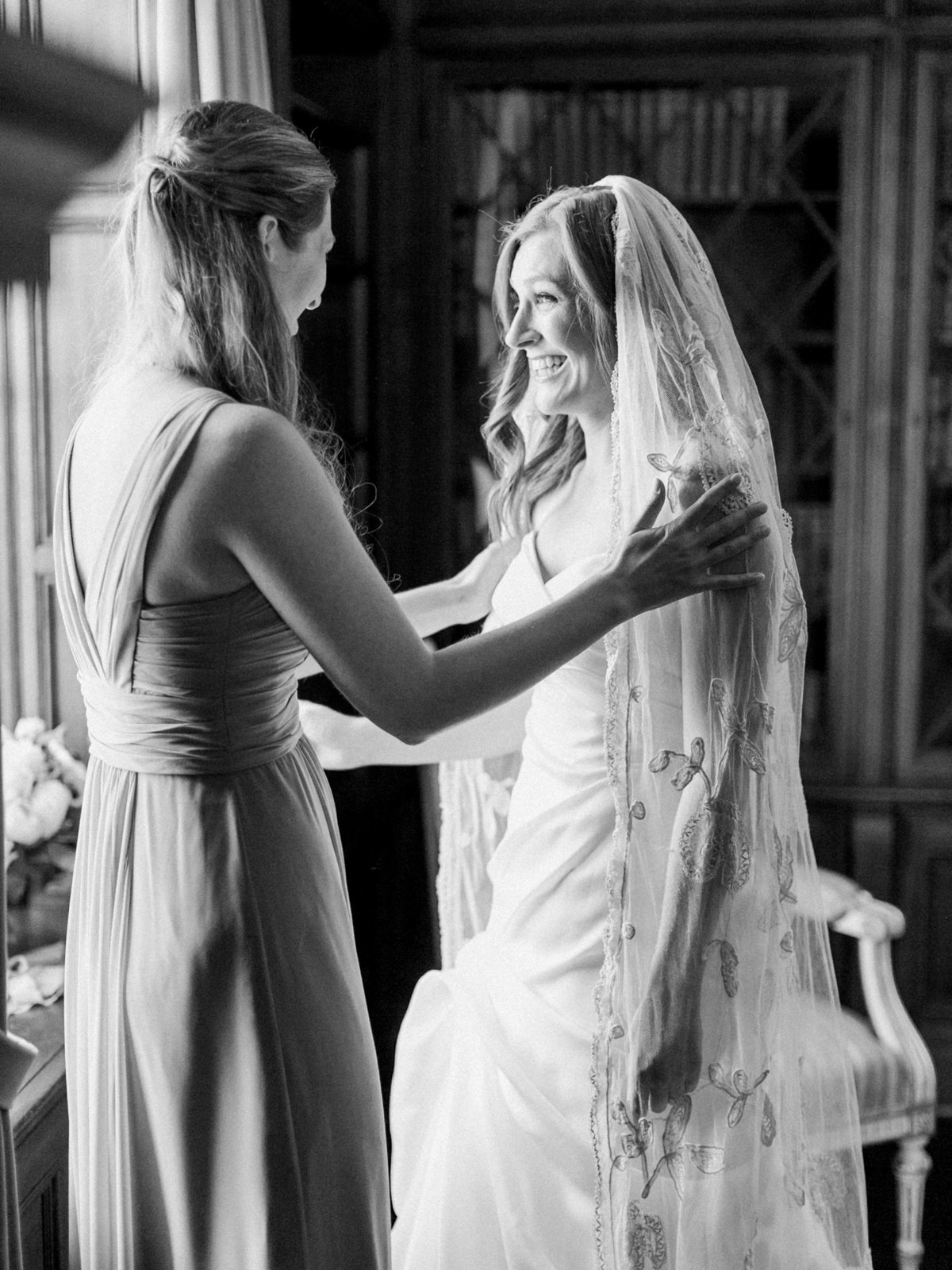 a bride putting on her wedding veil by annie eckstrom bridal