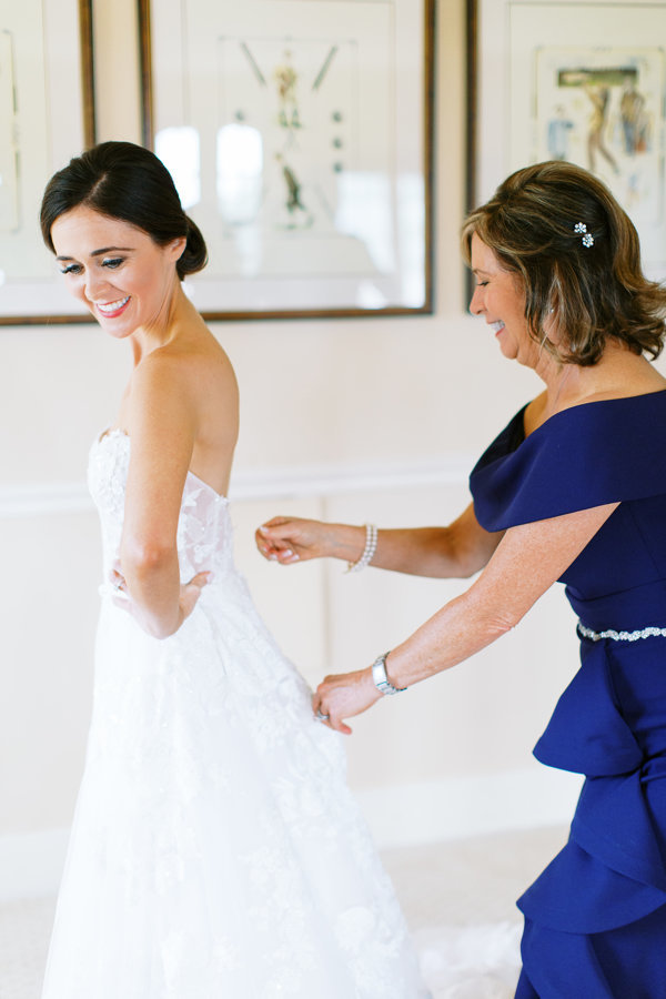 Bride-Getting-In-Gown-Mother-Helping