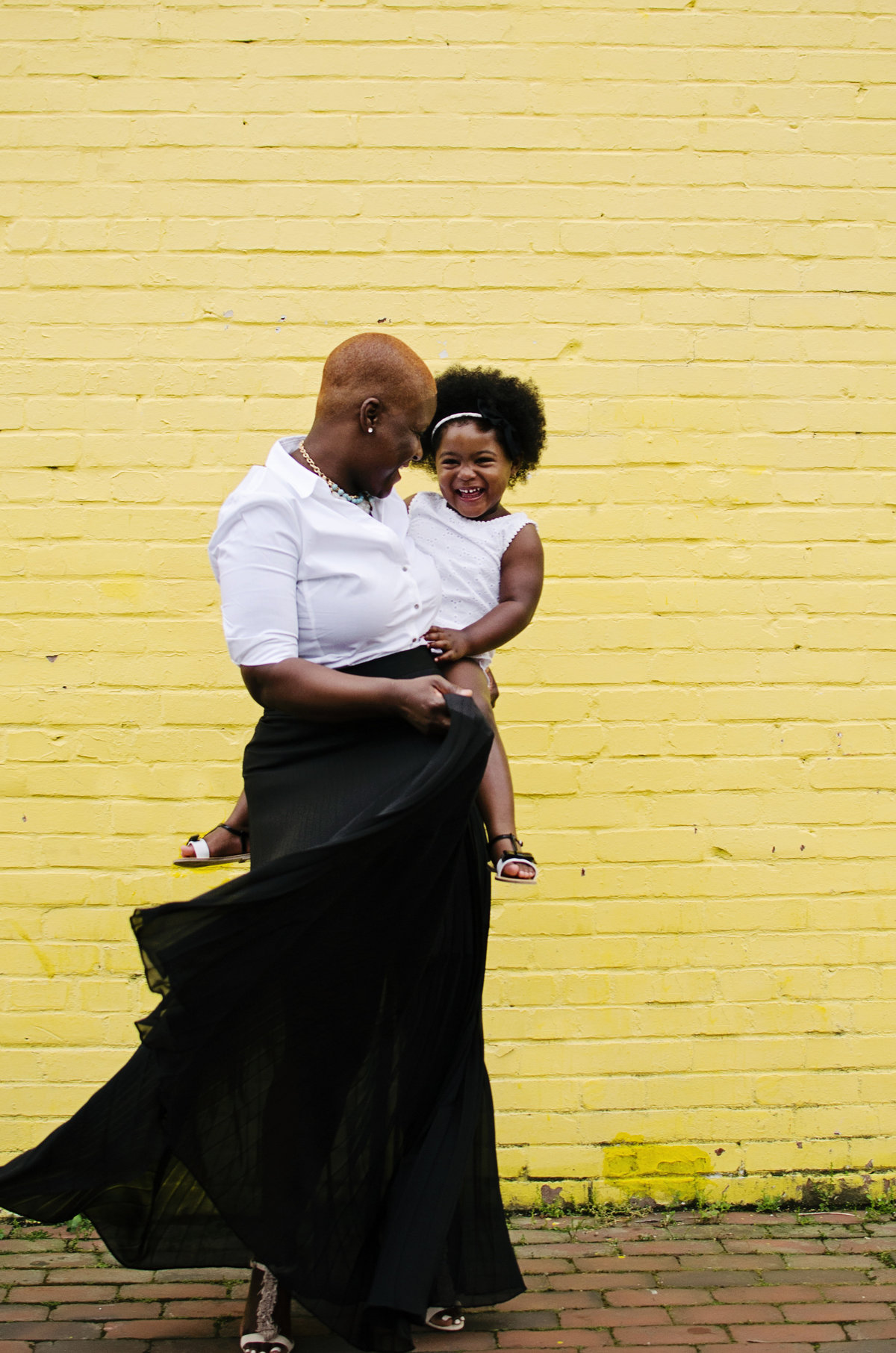 Portrait of a mother and daughter playing against a yellow brick wall in Old Town Alexandria taken by Sarah Alice Photography
