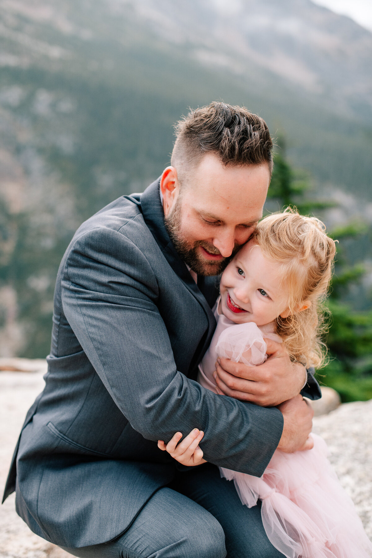 Groom hugging flower girl in pink dress at North Cascades elopement