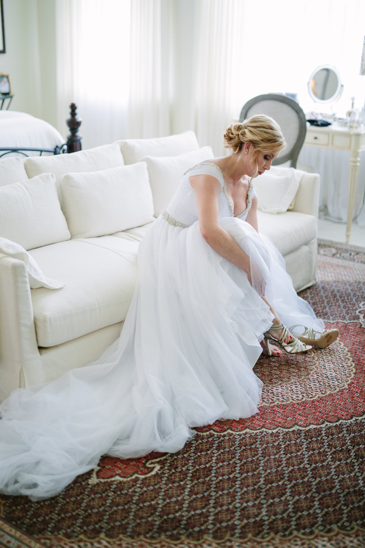 Bride putting her wedding shoes on during getting ready at home in San Antonio