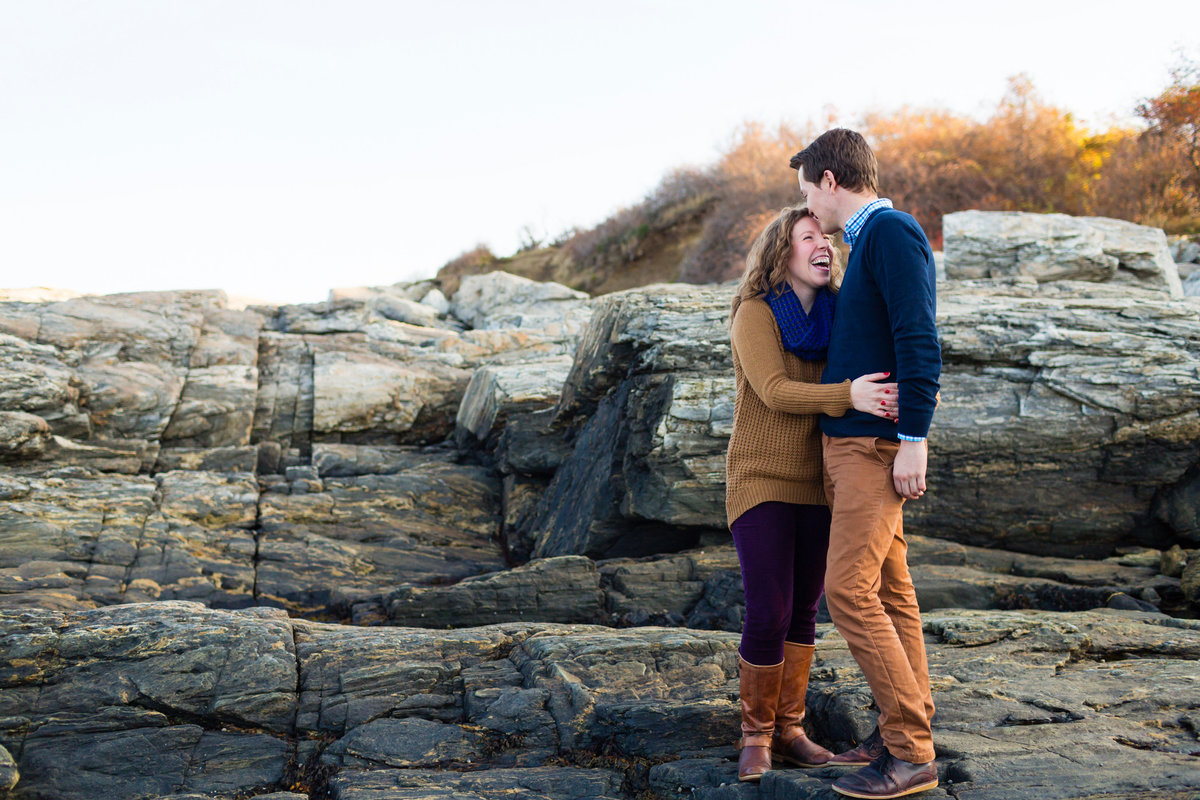 In Cape Elizabeth at Fort Williams the couple laughs on the rocks at their engagement session