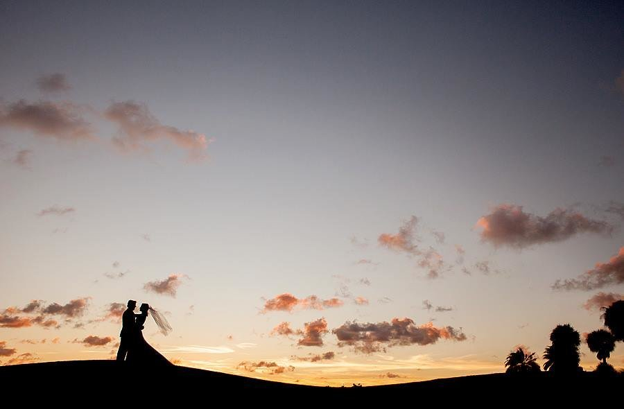 Couple standing on hill at sunset