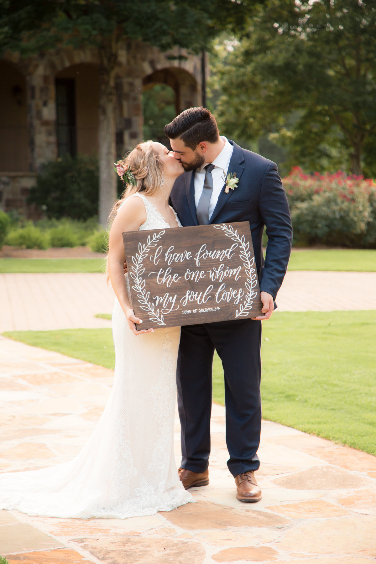 bride and groom kissing with sign for wedding
