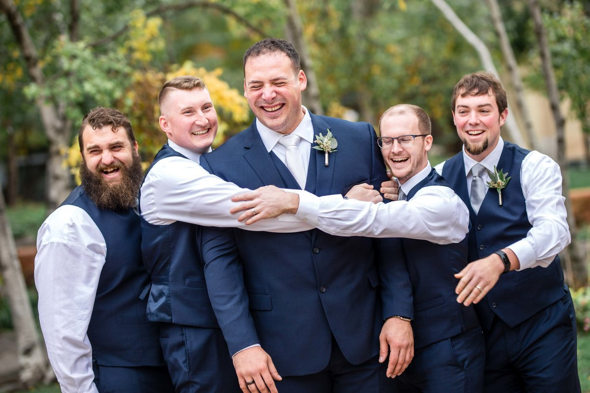 Groom being hugged by his groomsmen