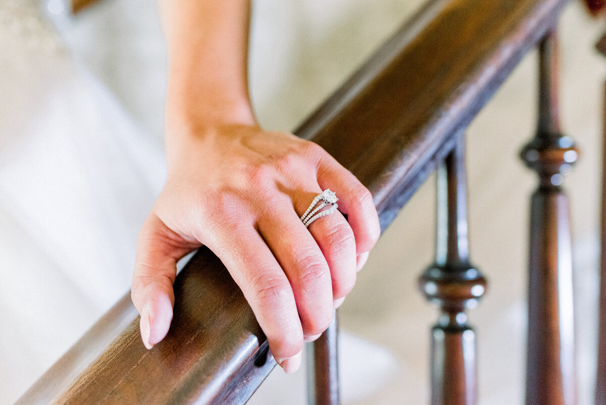 bride's hand on railing with wedding ring