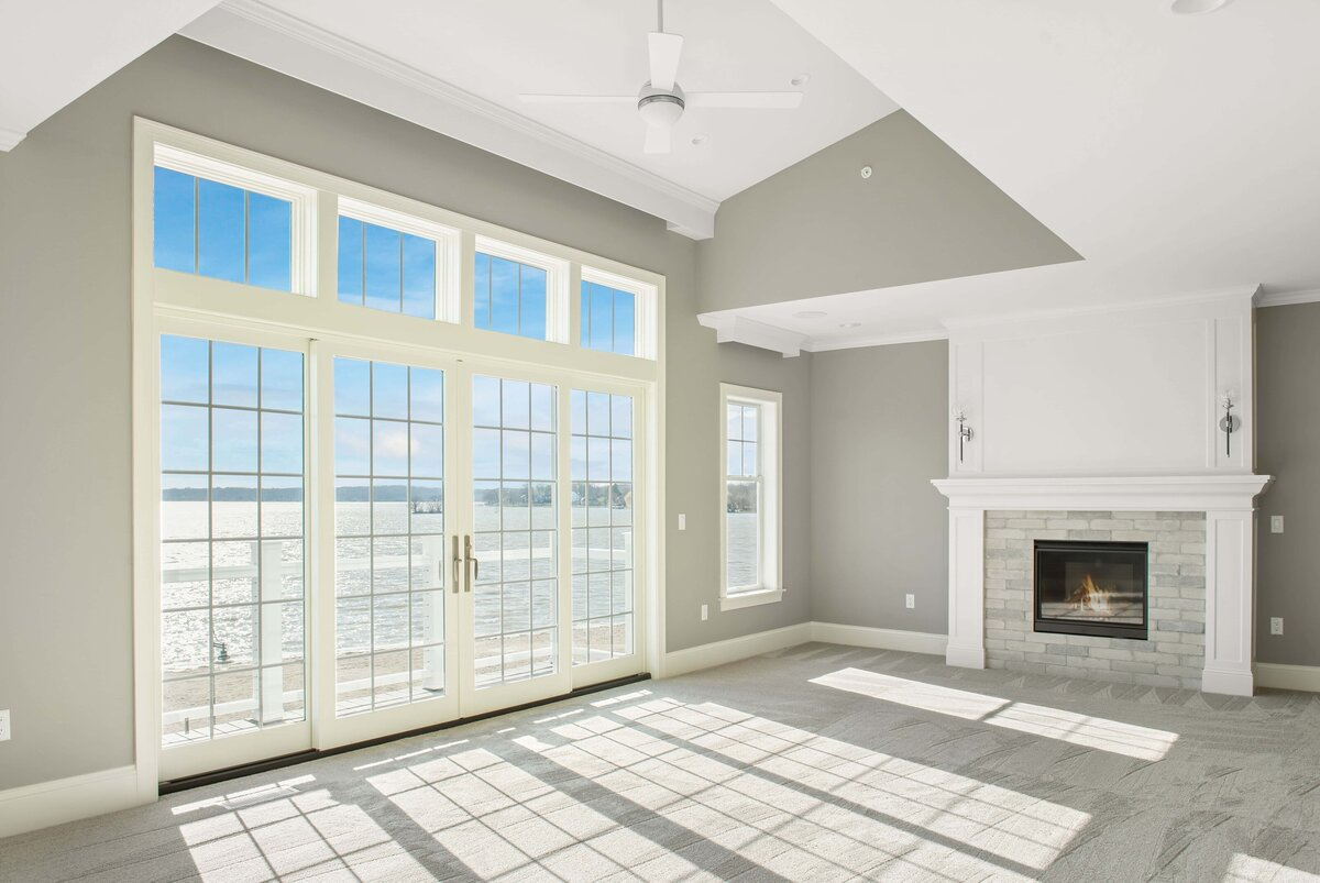 HDR beachfront living space floor to ceiling windows with a white fireplace to the right side.