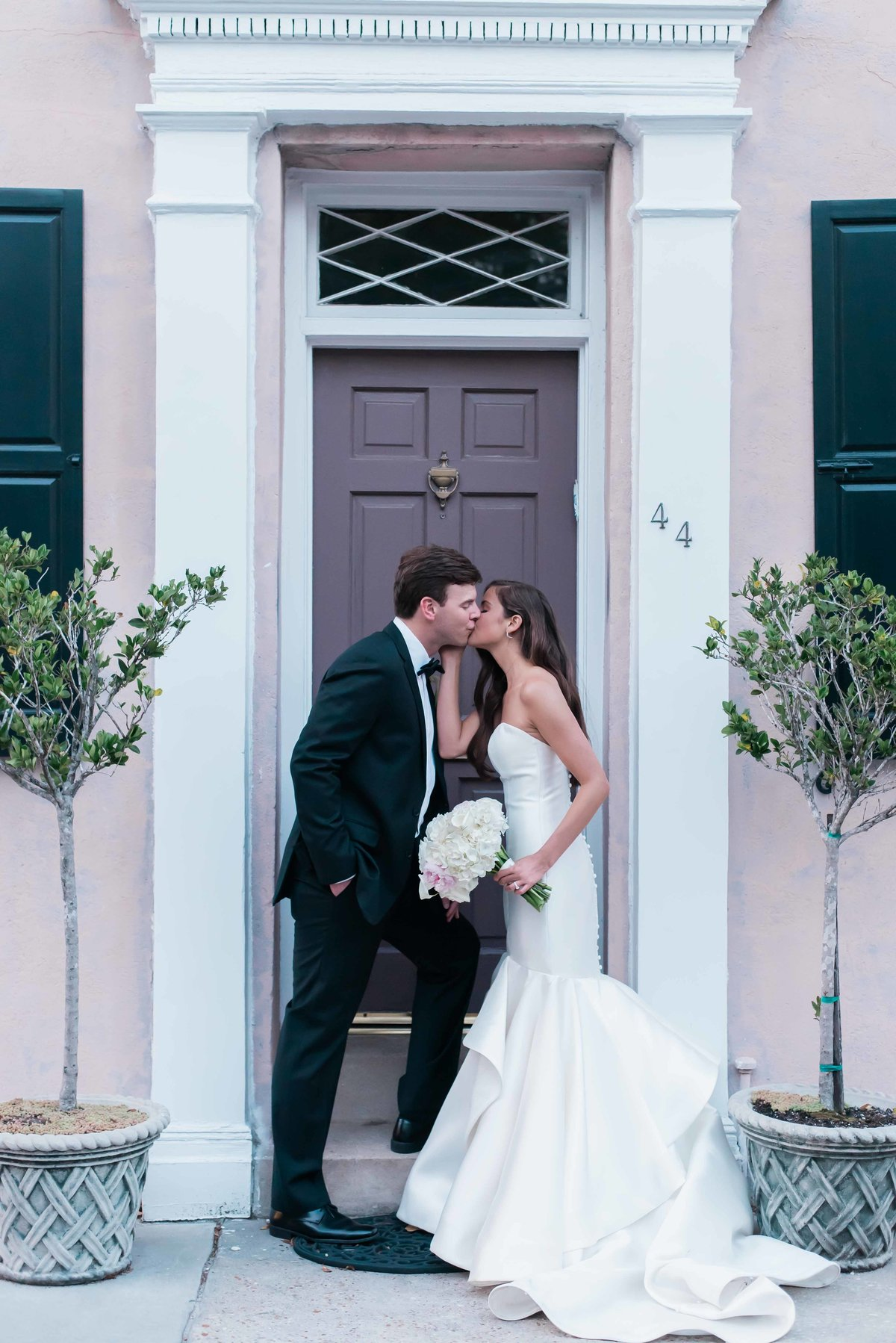 Bride and groom kiss in a traditional pink doorway in Charleston, SC