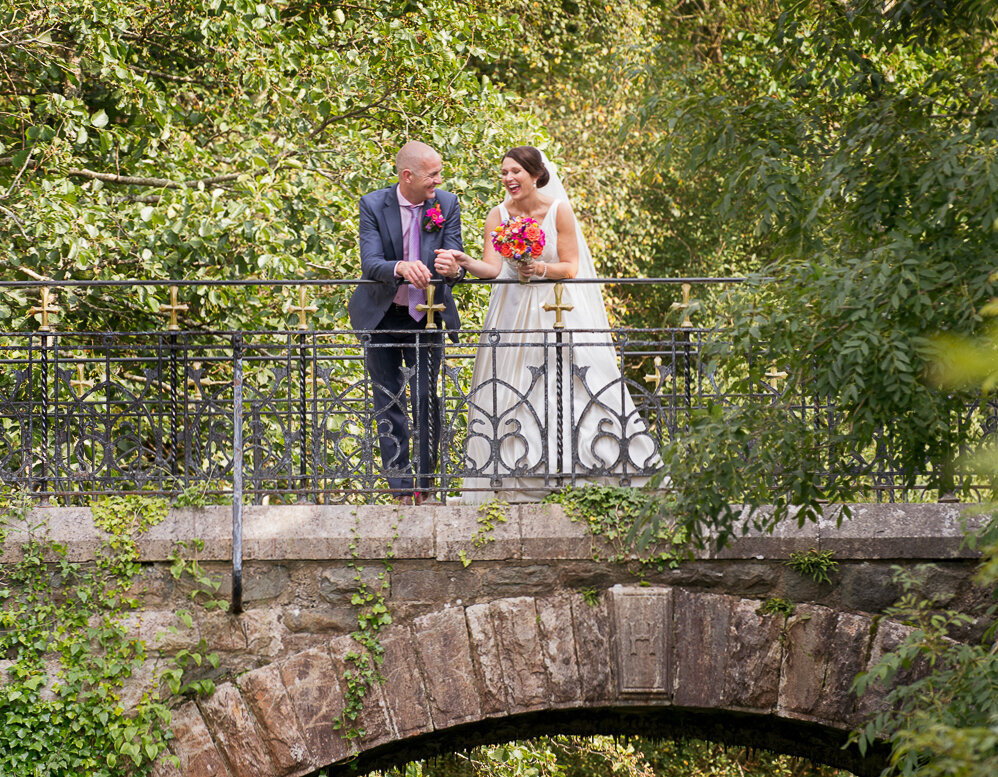 Bride with black hair, wearing a princess wedding dress and holding a colourful bouquet, standing on an old bridge with her groom wearing a blue suit and purple tie, surrounded by trees in Killarney National Park