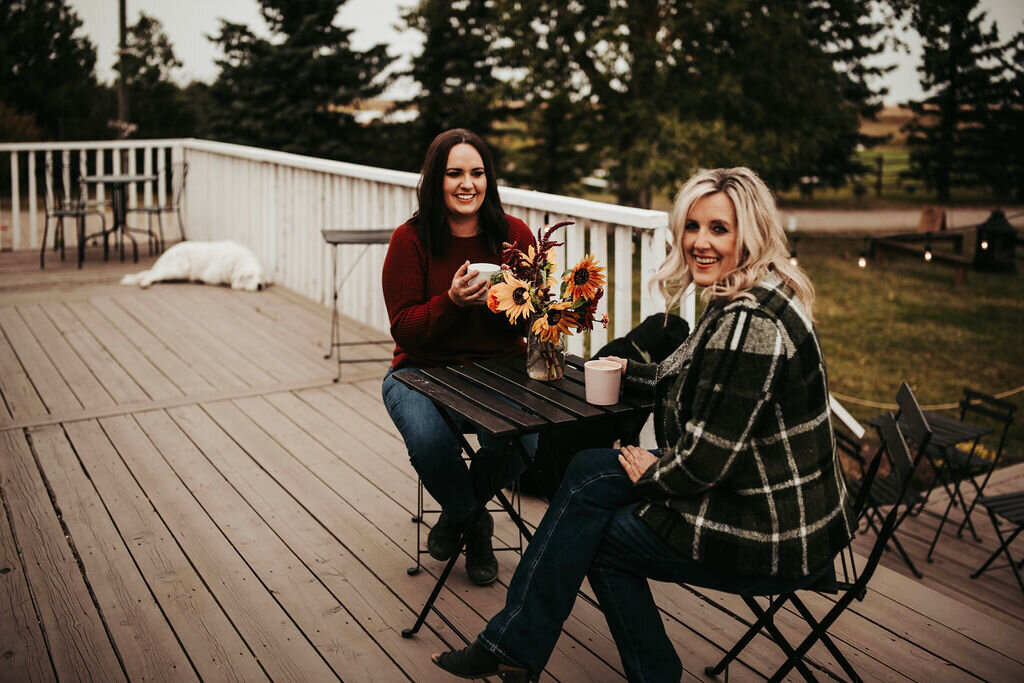 two women sitting on a porch drinking coffee