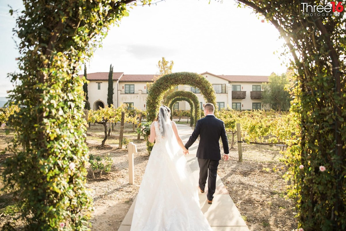 Bride and Groom walking under arch ways at Ponte Winery
