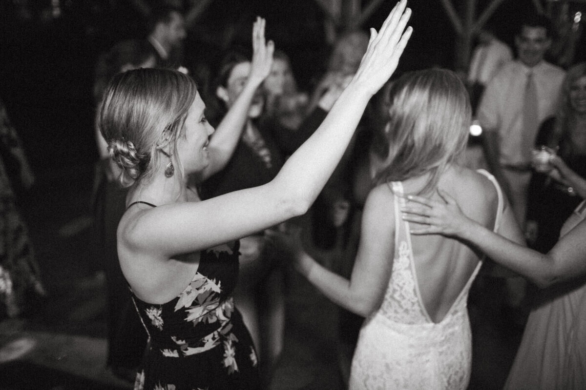 After the wedding, a woman raises her hands, dancing, while another woman dances next to the bride, with her hand on her back