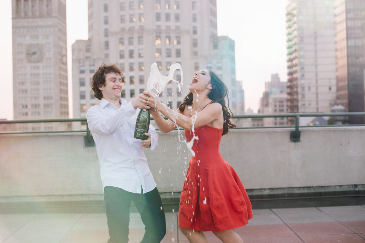 fun nyc new york city rooftop engagement pop champagne toast happy silly candid skyline