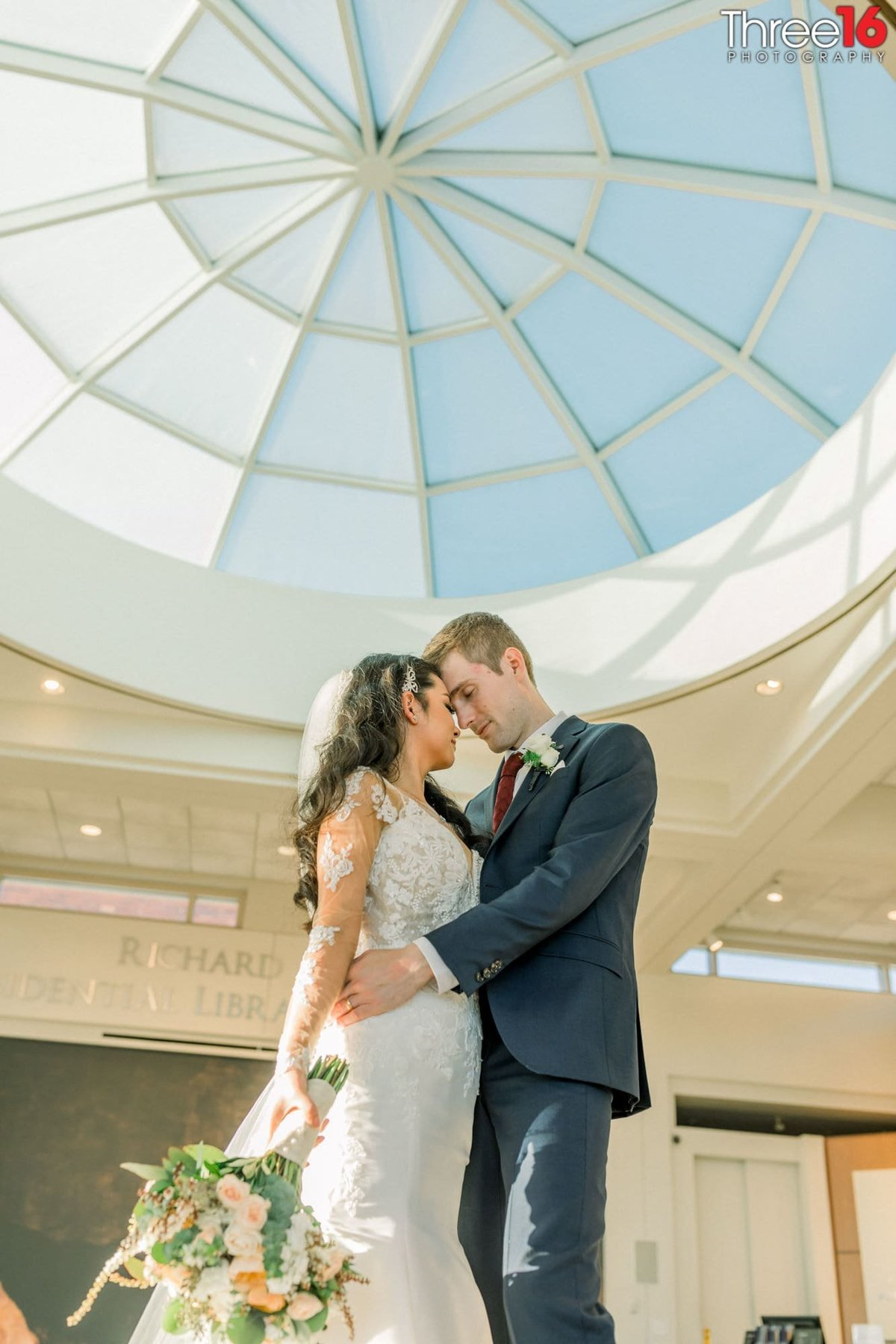 Bride and Groom embrace one another in the Richard Nixon Library lobby area