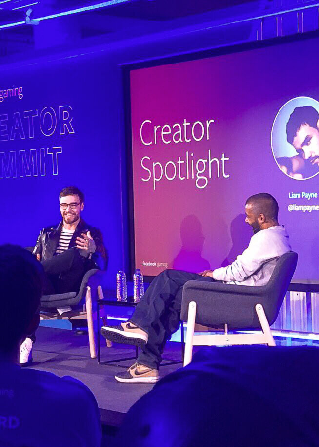 Liam Payne being interviewed for an event for Facebook Gaming on a purple lit stage.