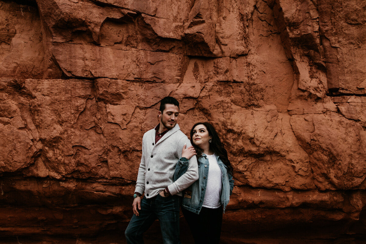 woman holding mans arm in front of red rocks