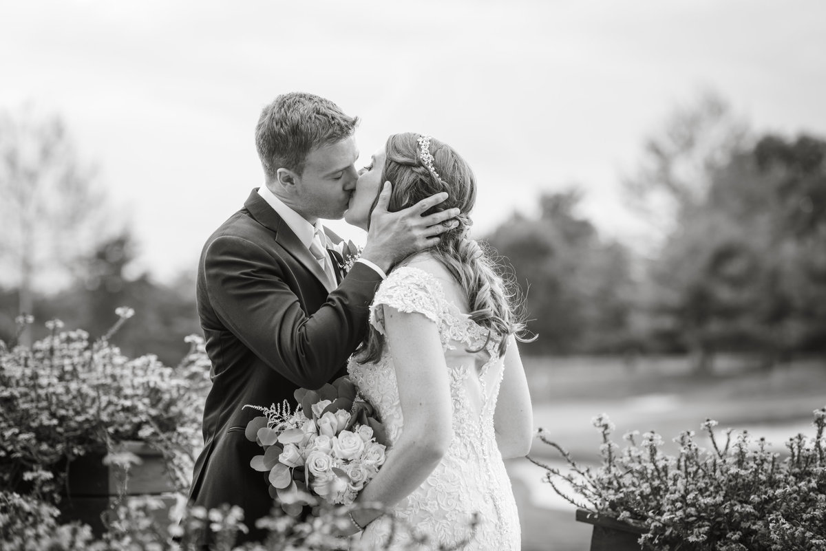 black and white photo of bride and groom kissing on golf course at Willow Creek Golf and Country Club