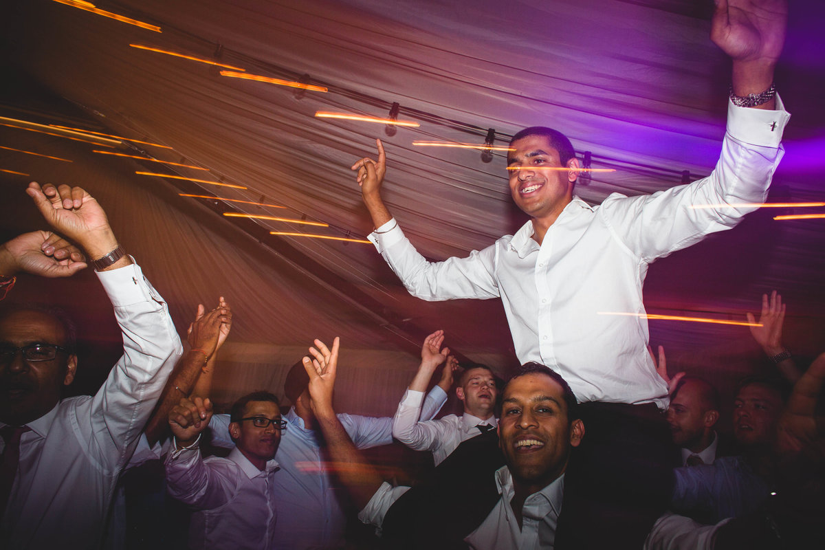 indian wedding photo of groom on friends shoulders dancing