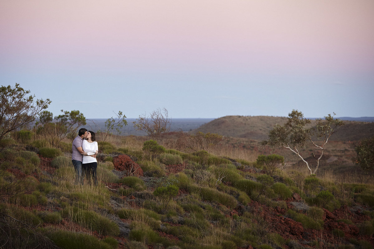Couple kissing at sunset amongst bushland