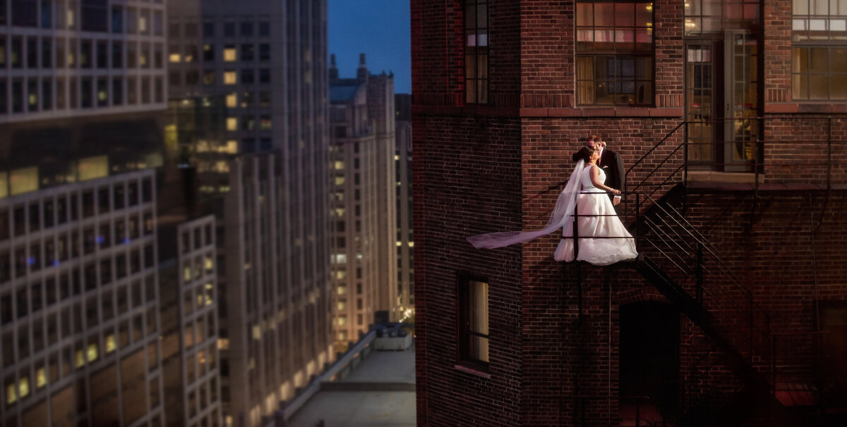 A Chicago wedding photographer captures the bride and groom on the fire escape at the Warwick Allerton hotel.
