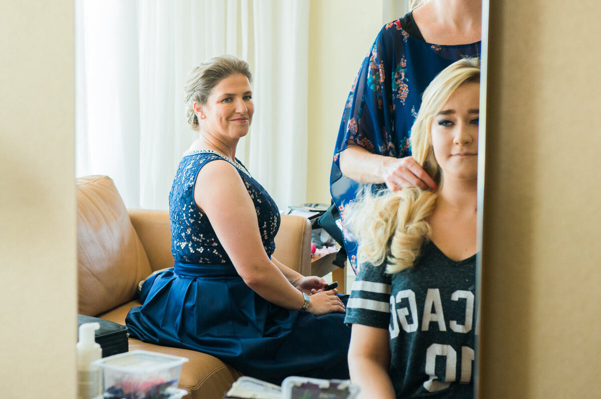 Bride in navy dress looking at sister having hair styled for wedding