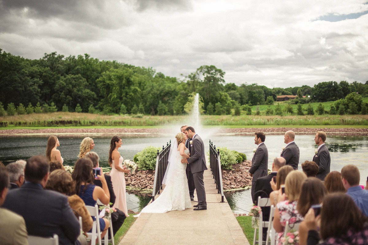wedding in front of the pond and fountain at orchard ridge farms the pavilion