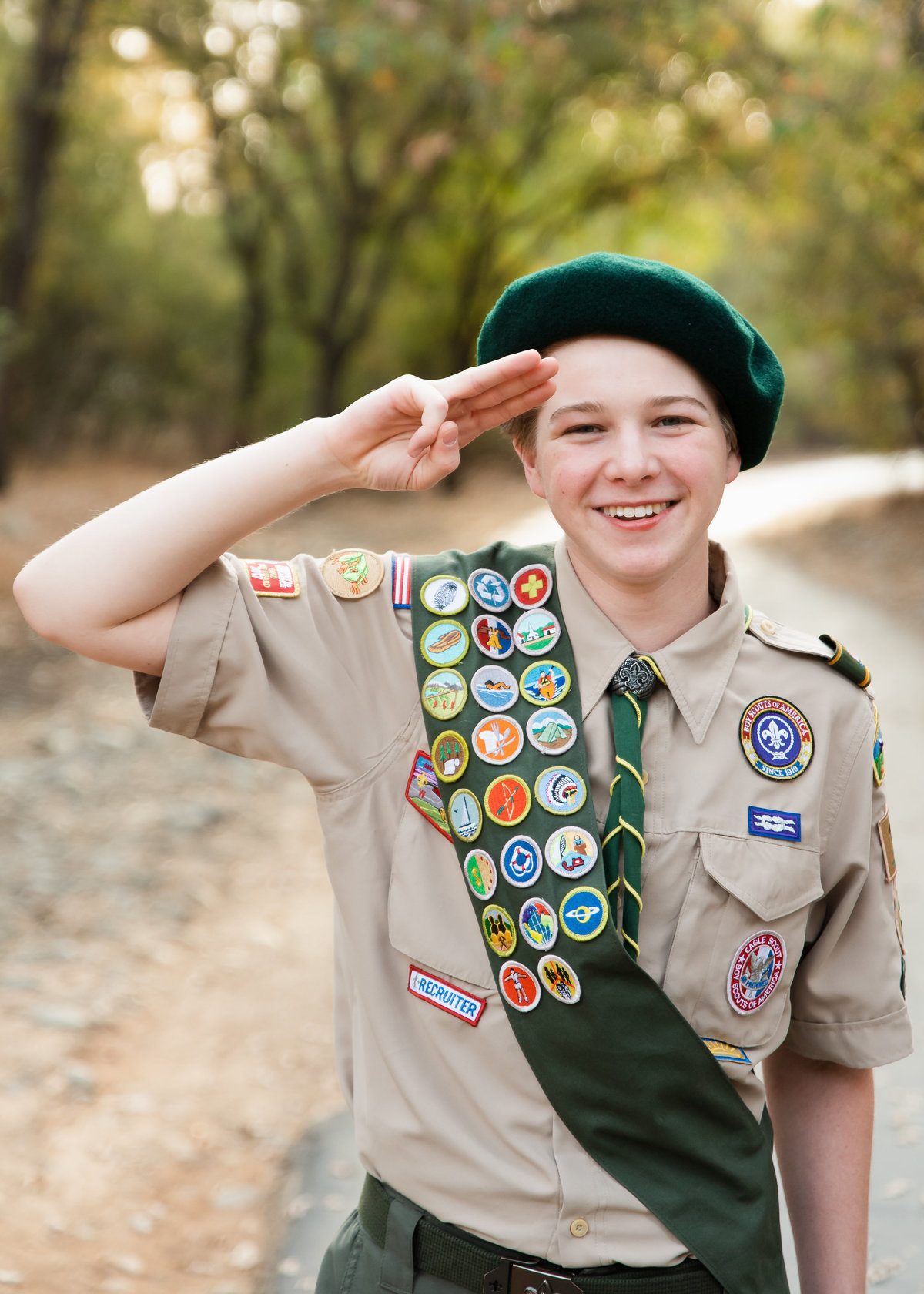 senior teen boy in scout uniform saluting