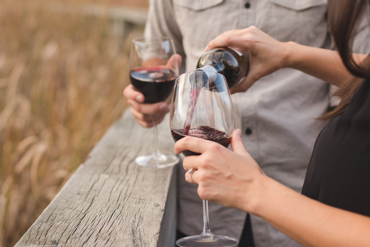 Couple pouring each other a glass of red wine during engagement session