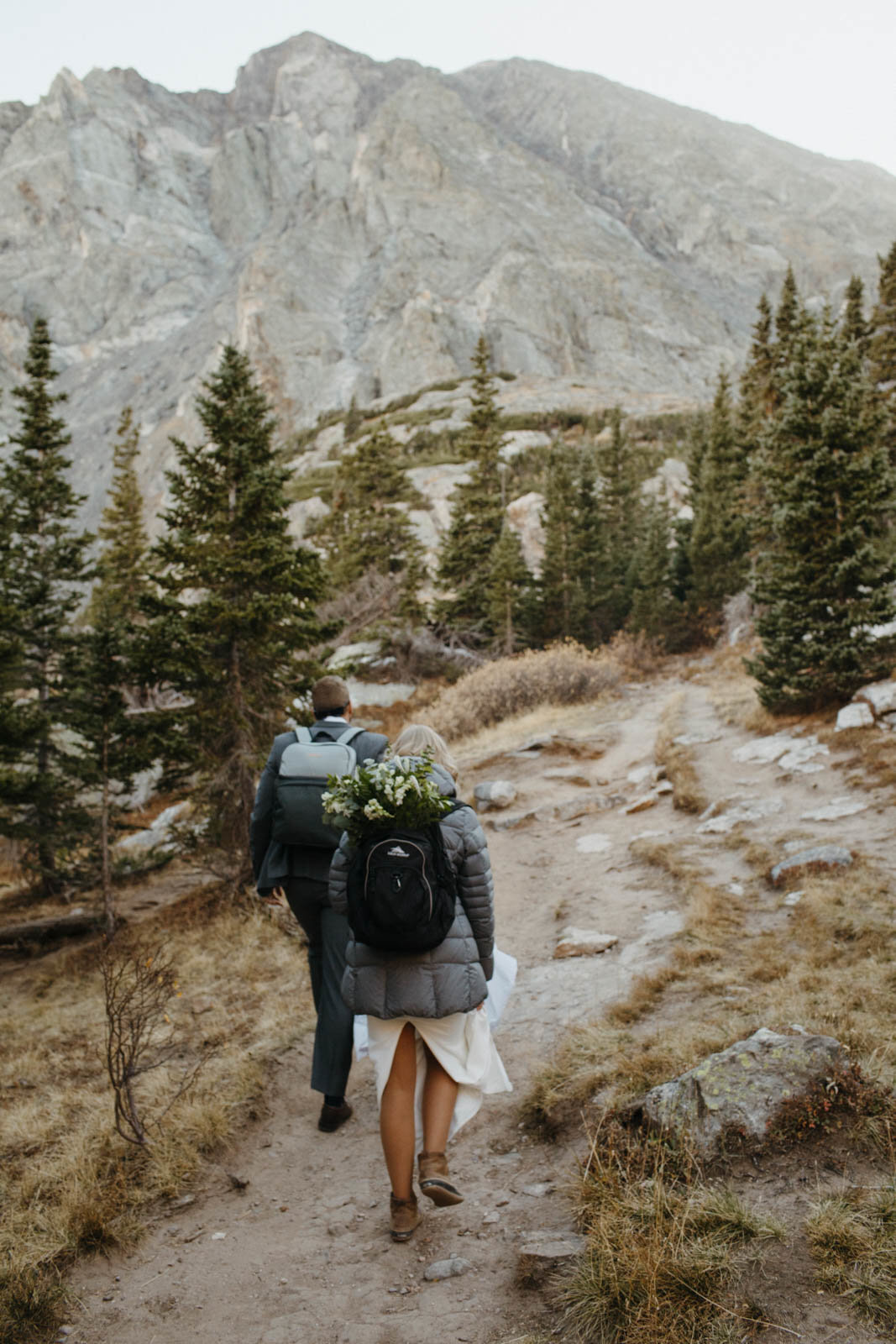 A photo taken behind a bride and groom hiking on a mountain, the bride has the flower bouquet attached to her backpack