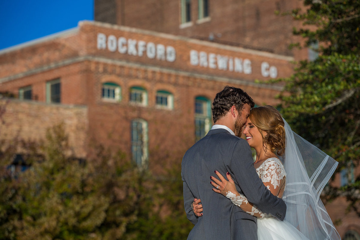 bride and groom hugging in front of prairie brewing company in rockford illinois