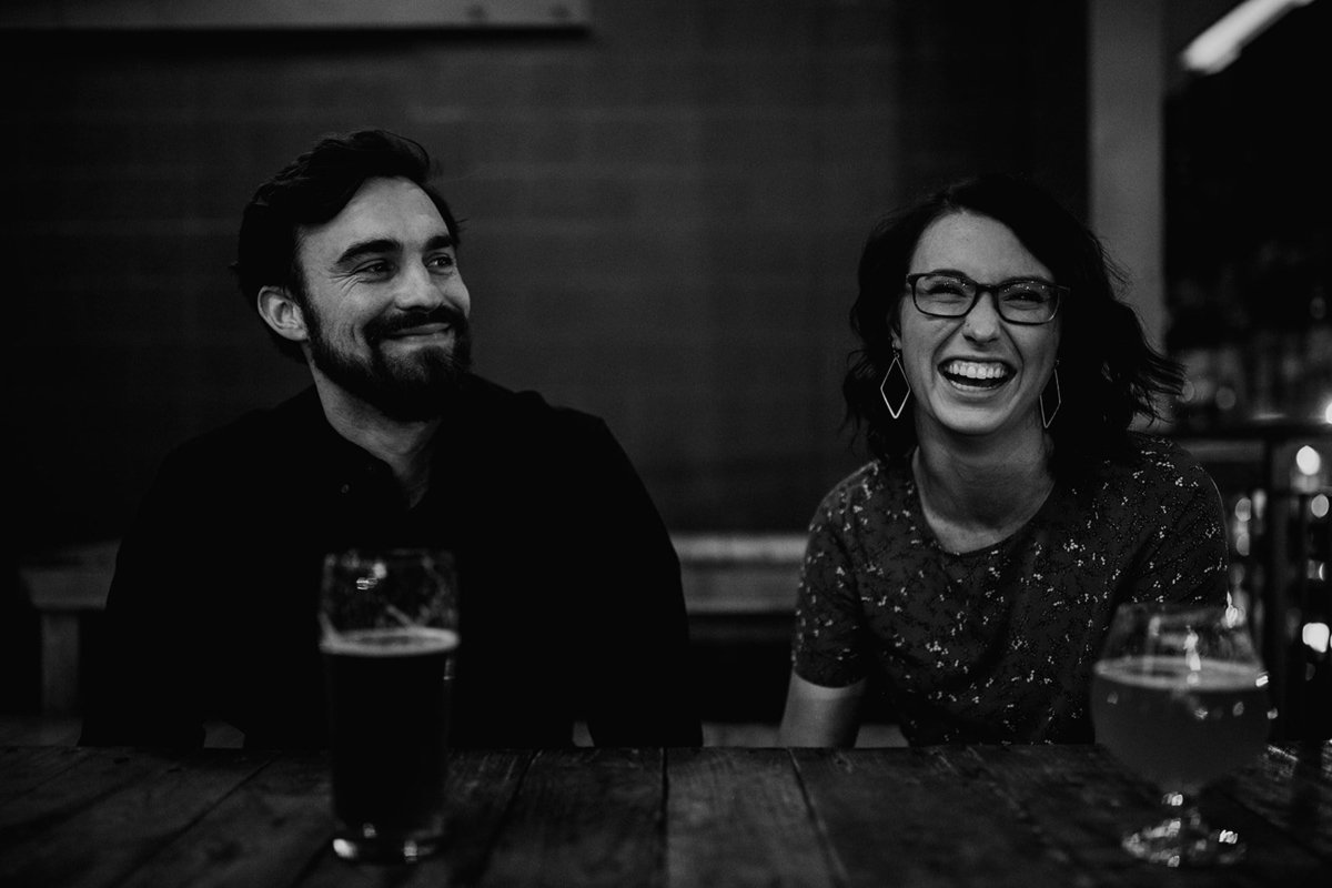 A black and white photo of a couple with drinks laughing.