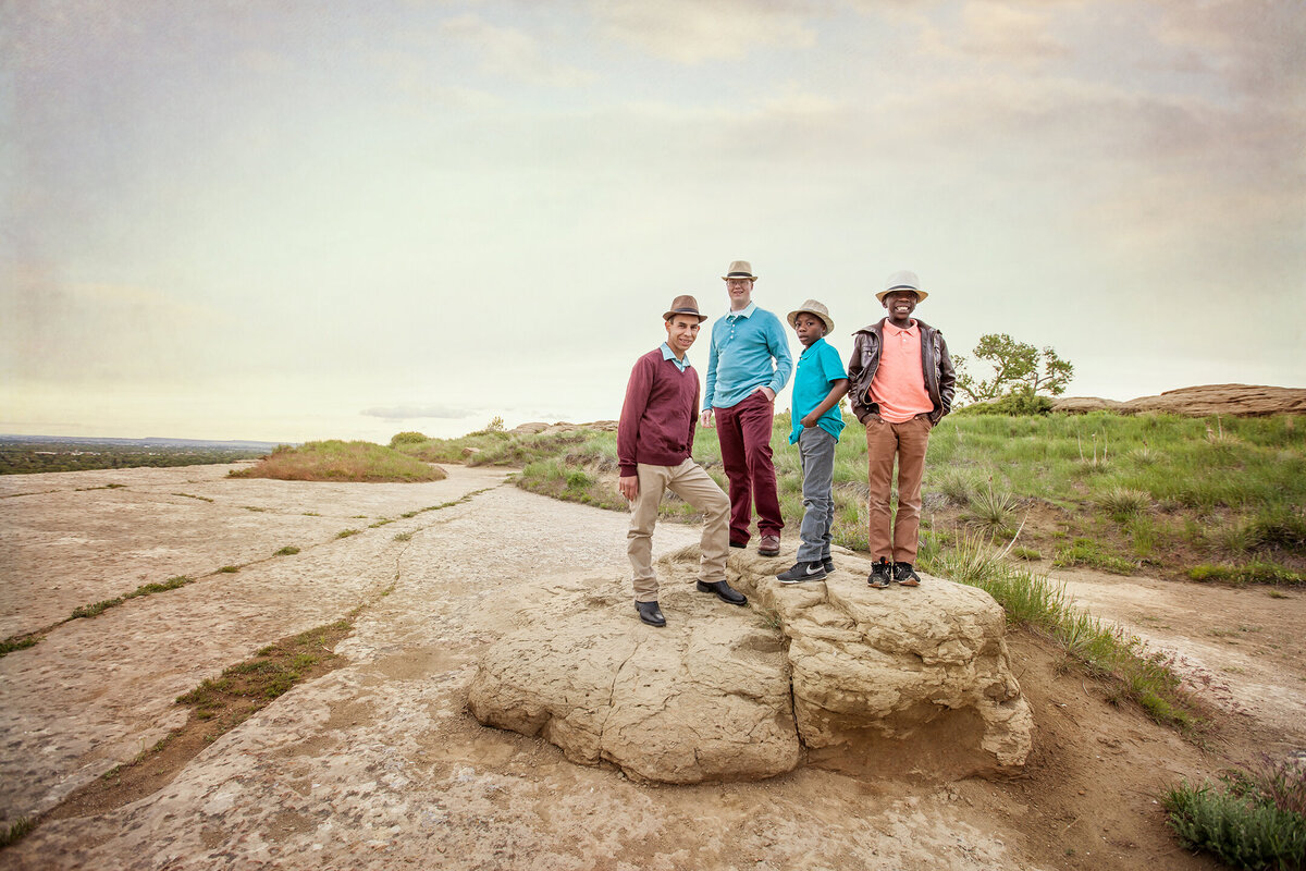 brothers standing on large sandstone rock with leading lines near sunset, teal, maroon, pink, gray and brown wearing hats and swords park next to airport in billings montana.