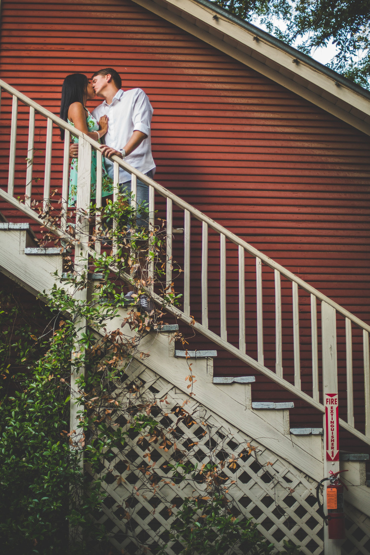 Couple kissing on the stairs at their engagement photography shoot at Ye Kendall Inn in Boerne, Texas.