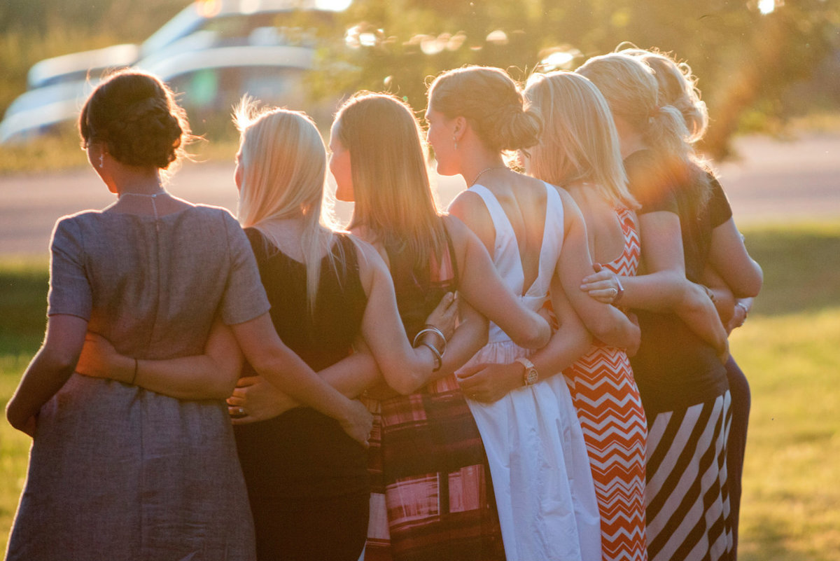 sunset shot with girls from behind, linking arms at reception, south dakota.