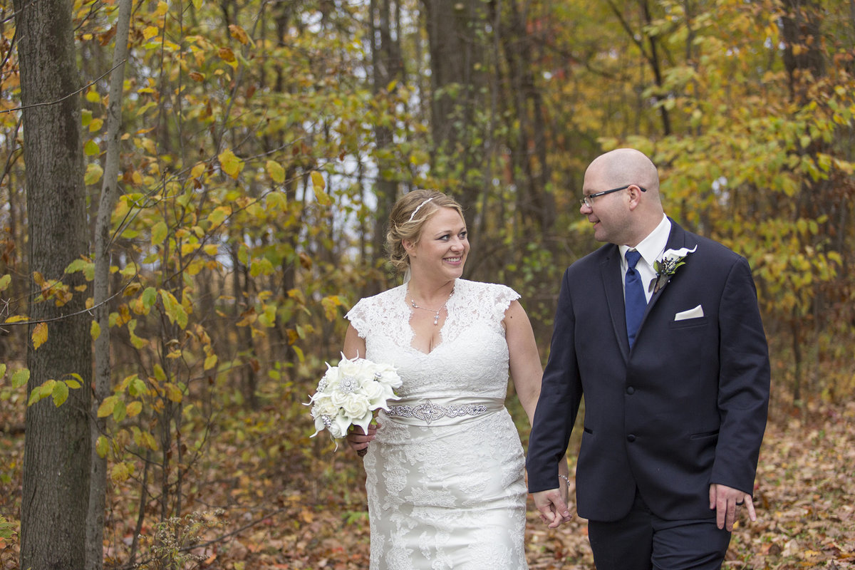 1LaineKippyWedding401 bride and groom walking in woods fall colors vintage wedding dress and blue tux cap sleeve wedding dress happy couple destination wedding photographer willow marie photography