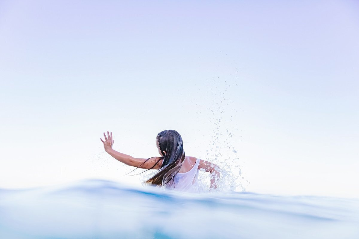 Unique portrait in the water of little girl waving arms and splashing