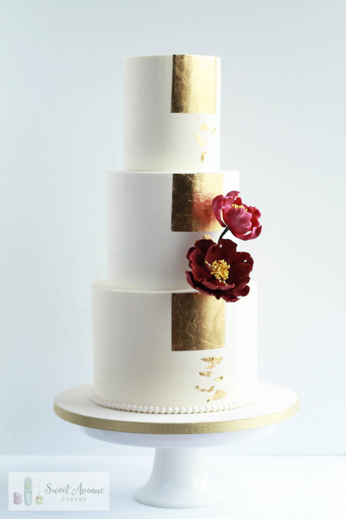 simple modern wedding cake  with gold foil and burgundy flowers