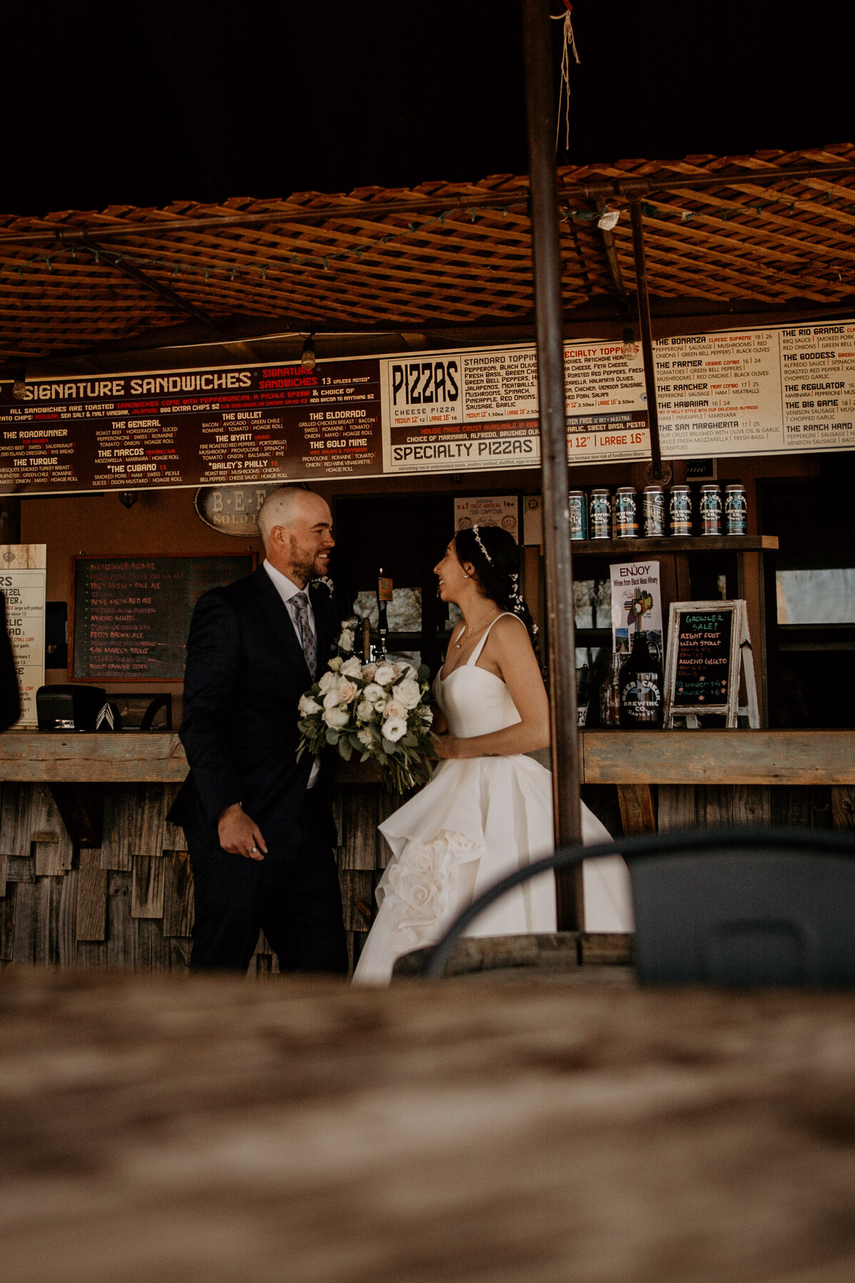 bride and groom standing together at a brewery in Santa Fe