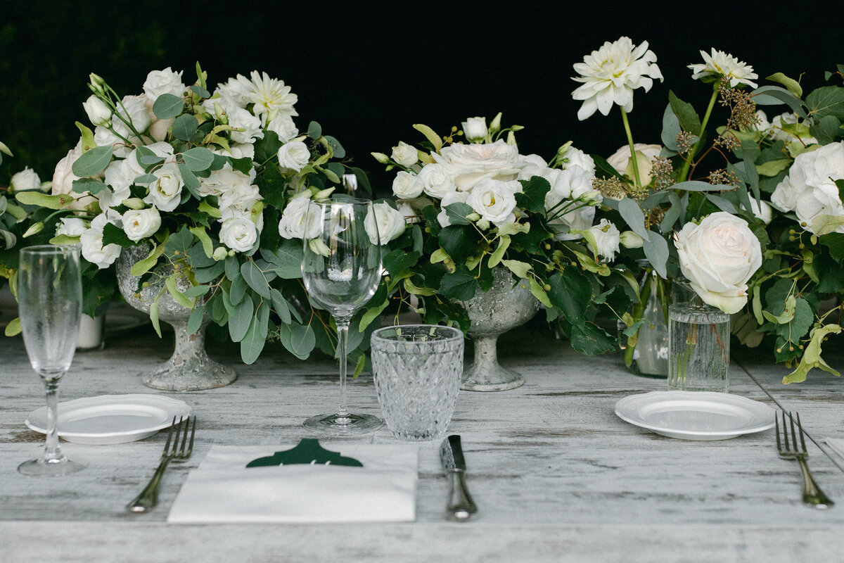 white and green floral arrangements on grey table at wedding