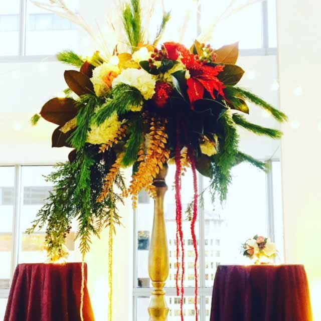 grand holiday buffet centerpiece with evergreen, gold leaves, red poinsettia, and white roses