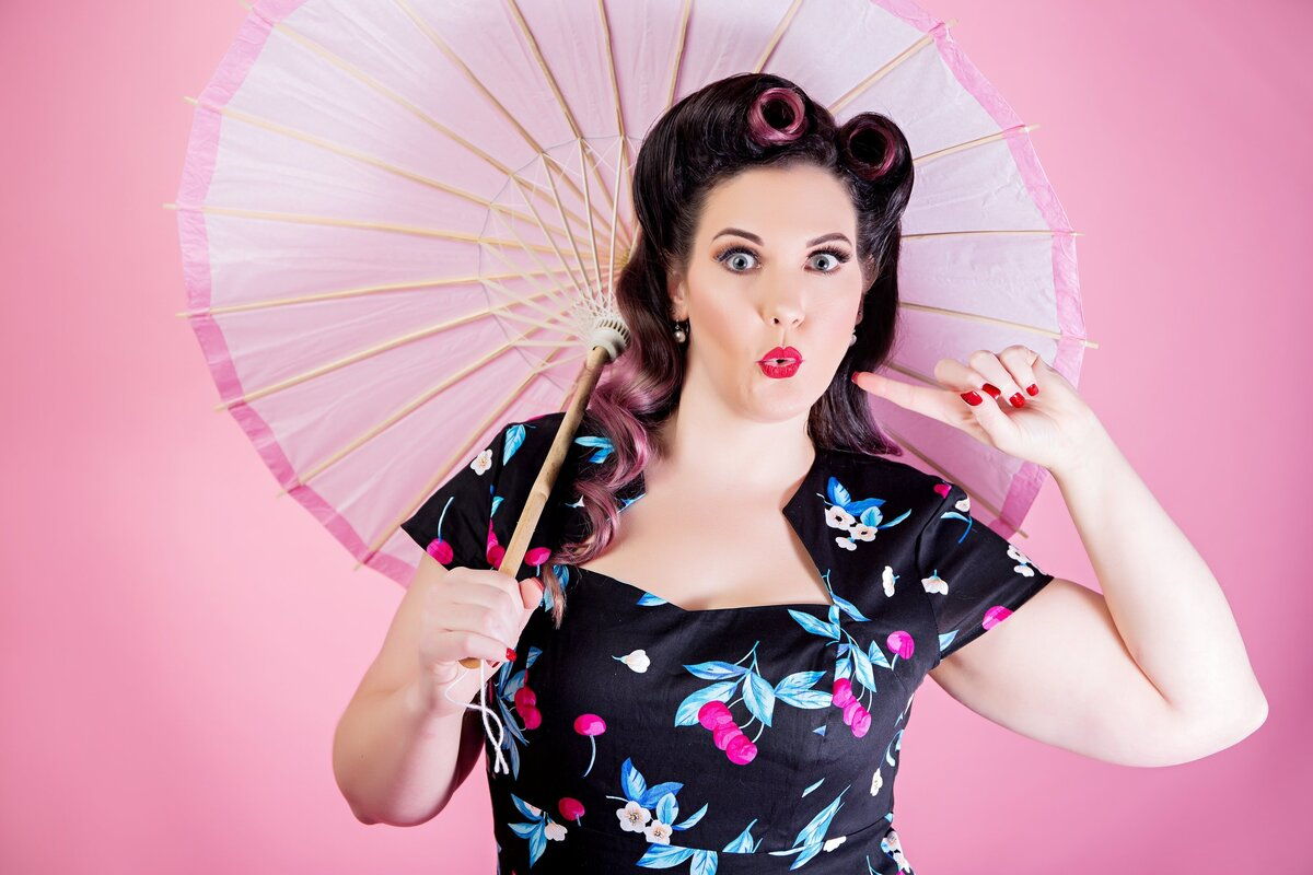 Brown and purple haired woman in a flower dress , holding an umbrella in front of a pink background. posing for a pinup photo